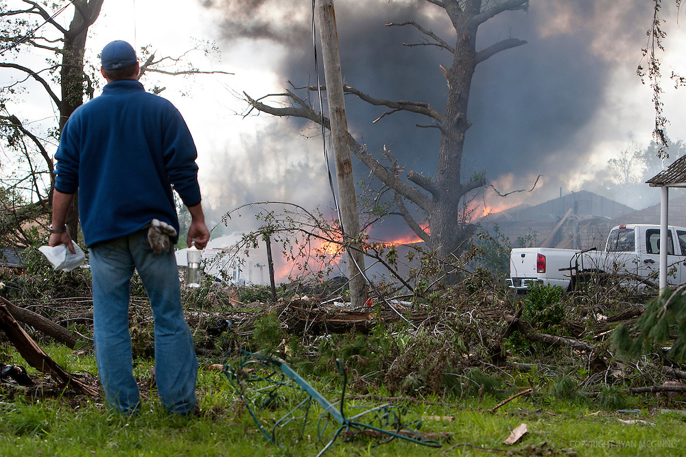A man watches a home burn in Joplin, Missouri, May 25, 2011.  On May 22, 2011, Joplin Missouri was devastated by an EF-5 tornado.