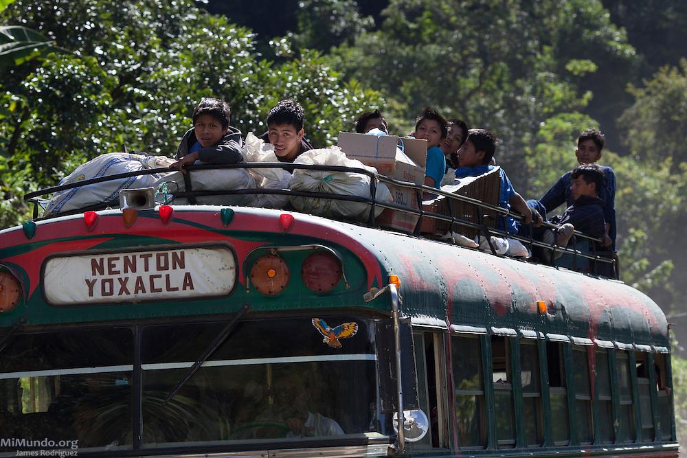 Young men ride on top of a Camioneta, or local bus, from San Miguel Acatán to Nentón. San Miguel Acatán, Huehuetenango, Guatemala. November 3, 2012.