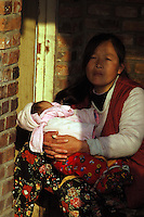 China, Beijing, Ping Fang Xiang, 2008. A mother sits in the doorway of her home in Ping Fang Xiang. Though new housing will soon be available, they are unlikely to be able to afford even the low prices offered by the central government..