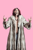 Portrait of young man in fur coat gesturing rock music sign over pink background