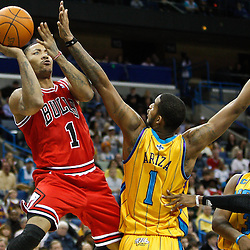 February 12, 2011; New Orleans, LA, USA; Chicago Bulls point guard Derrick Rose (1) shoots over New Orleans Hornets small forward Trevor Ariza (1) and point guard Chris Paul (3) during the fourth quarter at the New Orleans Arena.  The Bulls defeated the Hornets 97-88. Mandatory Credit: Derick E. Hingle