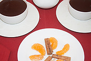 hot chocolate cups colose-up from above with orange slices on dark red tablecloth