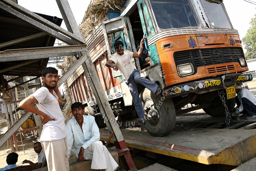 A truck driver and his co-workers are preparing to deliver their load of sugarcane inside the Daurala Sugar Works industrial complex, near Daurala village, Meerut District, Uttar Pradesh, India, on Monday, Apr. 14, 2008. Sugarcane-related manufactories, like sugar mills and distilleries rank between the 17 most polluting industries by the Indian Ministry of Environment and Forests and special conditions apply to the release of their wastewaters back into the environment. If Daurala Sugar Works, whose drain reaches the Kali river (East), have implemented a fairly efficient Effluent Treatment Plant, many in the sugarcane-rich area have not, and keep releasing contaminated water into nearby rivers. Even if levels of pollutants are believed to be largely reduced at the Complex, the Kali river (East) cannot absorb any more amount of wastewaters and its situation remains critically unhealthy.