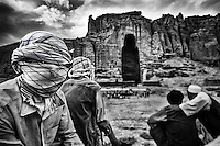 Afghan men gather to see children prepare for theatrical performance to appeal the danger of landmines in front of the remains of the statue of the big Buddha which was destroyed by Taliban in 2001.