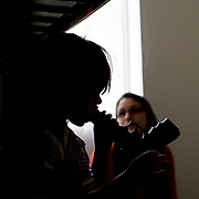 Child Protective Services Caseworker talks to a 6 year old girl asking questions about how her mother and her boyfriend treating her while she plays in a separate room during home visit. CPS keep an eye on the children when parents are abusive to drugs in this case. Caseworkers are scrutinize a lot because of lack of funding and tremendous workload.