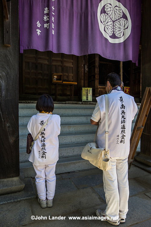 "The Shikoku Pilgrimage is a trail of 88 temples on the island of Shikoku. It is believed all 88 temples were visited by the famous Buddhist monk Kukai, founder of the Shingon school, who was born in Zentsuji Temple in 774. To complete the pilgrimage, it is not necessary to visit the temples in order. The pilgrimage is traditionally completed on foot, but modern pilgrims use cars, taxis, buses, bicycles or motorcycles. The walking course is approximately 1200km long and can take anywhere from 30 to 60 days to complete. ""Henro"" is the Japanese word for pilgrim - they are recognizable by their white clothing, sedge hats, and walking sticks."