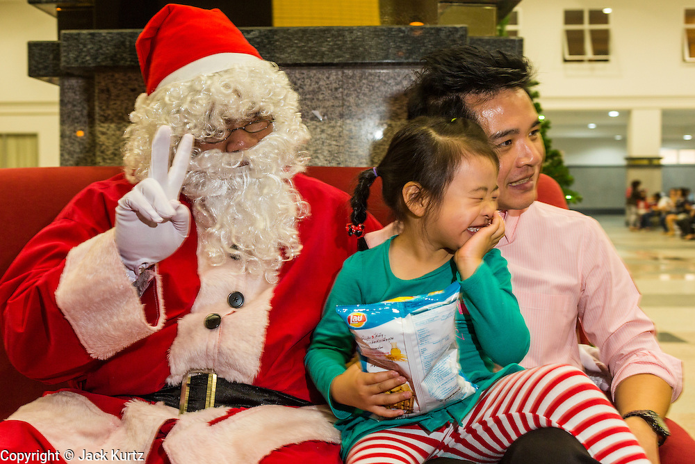24 DECEMBER 2013 - BANGKOK, THAILAND: A Thai man and his daughter pose with Santa Claus during Christmas observances at Holy Redeemer Church in Bangkok. Thailand is predominantly Buddhist but Christmas is widely celebrated throughout the country. Buddhists mark the day with secular gift giving but there are about 300,000 Catholics in Thailand who celebrate religious Christmas. Catholics first came to Thailand (then Siam) in 1567 as chaplain for Portuguese mercenaries in the employ of the Siamese monarchy. There has been a continuous Catholic presence in Thailand since then.   PHOTO BY JACK KURTZ