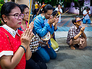 "02 JUNE 2017 - SAMUT SAKHON, THAILAND: People pray as the City Pillar Shrine is taken through the streets of Samut Sakhon during the procession honoring the shrine. The Chaopho Lak Mueang Procession (City Pillar Shrine Procession) is a religious festival that takes place in June in front of city hall in Samut Sakhon. The ""Chaopho Lak Mueang"" is  placed on a fishing boat and taken across the Tha Chin River from Talat Maha Chai to Tha Chalom in the area of Wat Suwannaram and then paraded through the community before returning to the temple in Samut Sakhon. Samut Sakhon is always known by its historic name of Mahachai.      PHOTO BY JACK KURTZ"