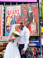 Manhattan, New York, USA: A bride and groom pose for pictures in Times Square, NYC, on Tuesday, January 24, 2012, after their City Hall marriage ceremony. Temperatures were unseasonably warm, reaching 52°F / 11°C mid-afternoon.