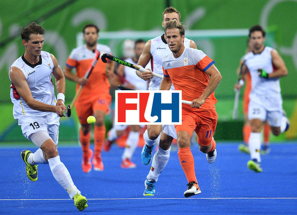 Belgium's Felix Denayer (L) vies with Netherland's Jeroen Hertzberger (2nd R) during the men's semifinal field hockey Belgium vs Netherlands match of the Rio 2016 Olympics Games at the Olympic Hockey Centre in Rio de Janeiro on August 16, 2016.  / AFP / Carl DE SOUZA        (Photo credit should read CARL DE SOUZA/AFP/Getty Images)