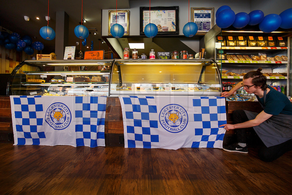 © Licensed to London News Pictures. 03/05/2016. Leicester, UK. Brü Cafe staff putting up Leicester City flags up in their coffee shop as fans celebrate Leicester City winning the 2016 Premier League title the day before in Leicester city centre on Tuesday, 3 May 2016.  Photo credit: Tolga Akmen/LNP