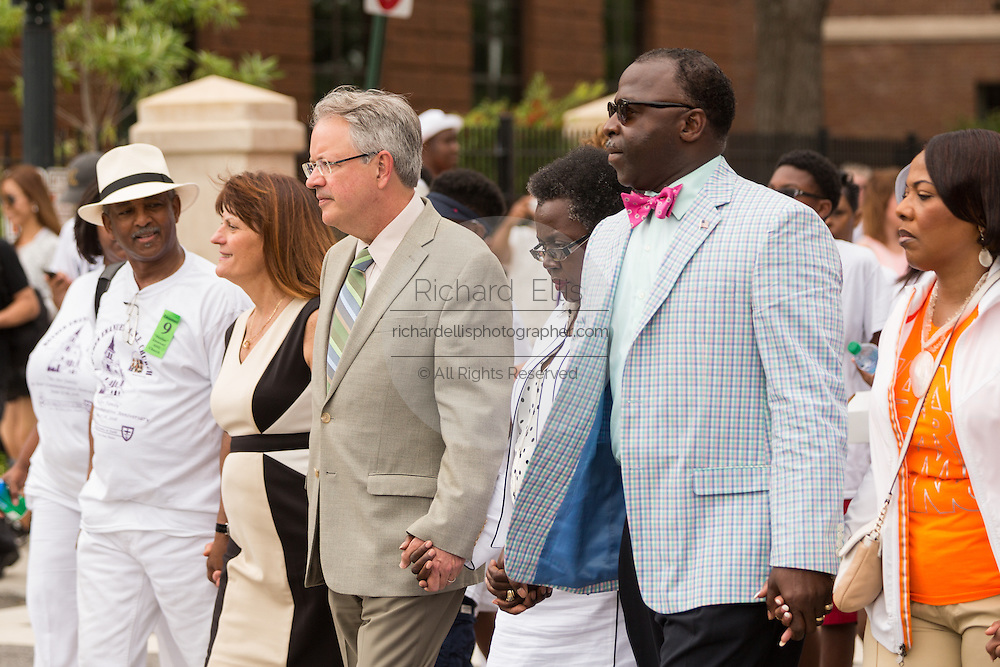 The Mayor of Charleston John Tecklenburg, center, joins family members of the nine people killed at the Emanuel AME Church on the anniversary of the mass shooting June 18, 2016 in Charleston, South Carolina. Nine members of the historic Mother Emanuel African Methodist Episcopal Church were gunned down during bible study at the church on June 17, 2015.