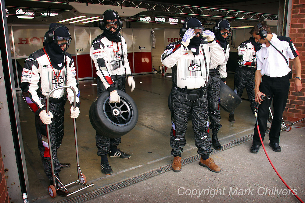 Journalist Dan Jones (2nd L) and his team undertake a pit stop challenge where they changed tyres and performed other duties of a proffessional pit stop crew. Also meeting Jenson Butten at Brands Hatch race track. Here Dan secures the teams driver.