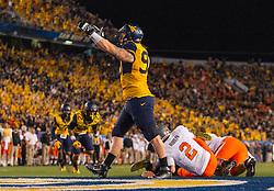 Oct 10, 2015; Morgantown, WV, USA; Oklahoma State Cowboys quarterback Mason Rudolph is sacked by West Virginia Mountaineers defensive lineman Kyle Rose for a safety during the second quarter at Milan Puskar Stadium. Mandatory Credit: Ben Queen-USA TODAY Sports