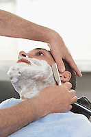 Barber shaving man in barber shop close-up