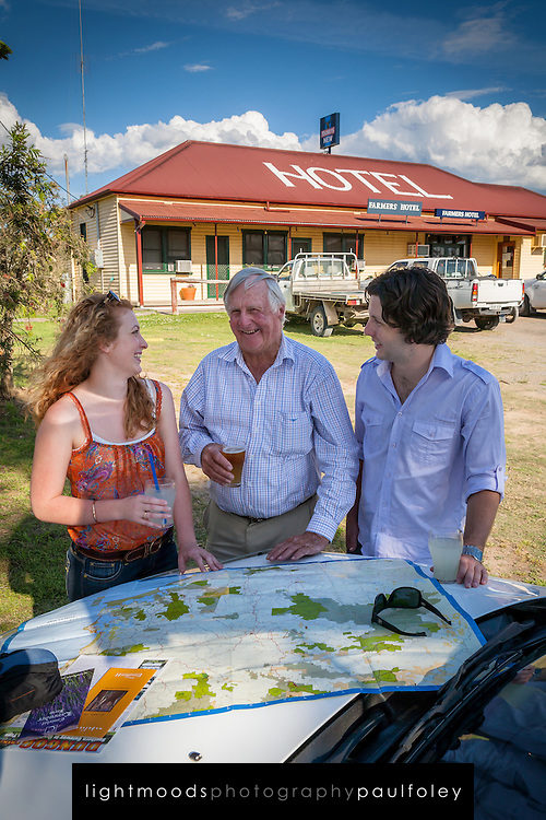 Young Couple receiving directions from a helpful local in rural Australia outside a country pub.