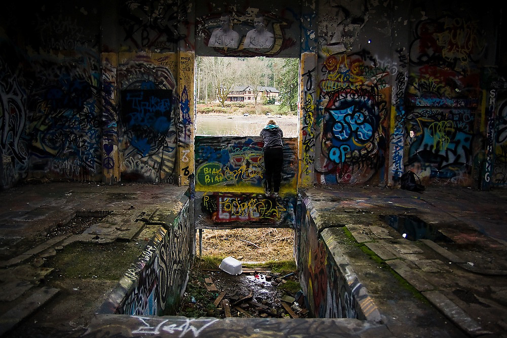 Anna Reiser looks out a window, towards a large mansion, in an abandoned warehouse covered in graffiti in Blakely Harbor Park on Bainbridge Island, Washington. The park is the former site of Port Blakely Mill, which was one of the world's largest sawmills in the late 19th century.