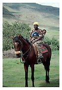A Basutho mother and her child on their Basutho Pony. Her baby is securely lodged in a papoose on her back. Lesotho is a landlocked mountain kingdom in Southern Africa.