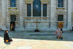 © Licensed to London News Pictures. 25/06/2020. LONDON, UK.  Sally, a priest of the church, (L) and Carol, a congregation member, kneel in the new outdoor Prayer Garden in the courtyard of St Martin-in-the-Fields, Trafalgar Square, where all are welcome to meditate, pray and discover peace and stillness at the heart of London.  The UK government has relaxed coronavirus pandemic lockdown restrictions allowing churches and other places of worship to open for private prayer from 15 June and, in the latest change, collective worship and communal prayer will be allowed from 4 July.  Currently, many churches are offering online services to their congregations. Photo credit: Stephen Chung/LNP
