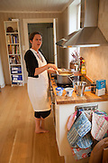 The Glad Ostensen family in Gjerdrum, Norway. Anne Glad Fredricksen, 45, as she prepares the evening meal after work in their farmhouse kitchen. Model-Released.