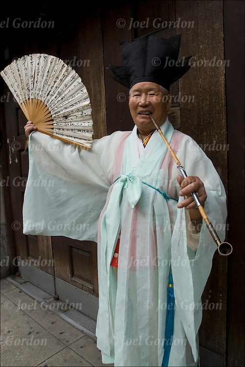 Annual Korean Harvest Parade in New York City. Portrait of  Korean-American elderly man  with opium pipe smiling wearing traditional white Korean folk costume.