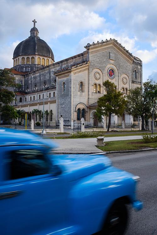 HAVANA, CUBA - CIRCA MARCH 2017: Old classic car drives in front of the Historic Church Jesús de Miramar.