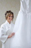 Bride in bathrobe touching wedding dress