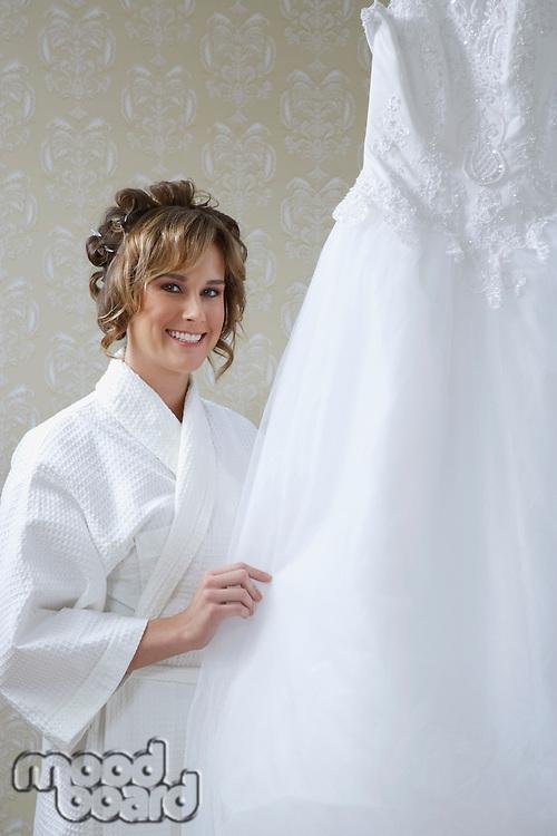 Bride in bathrobe touching wedding dress