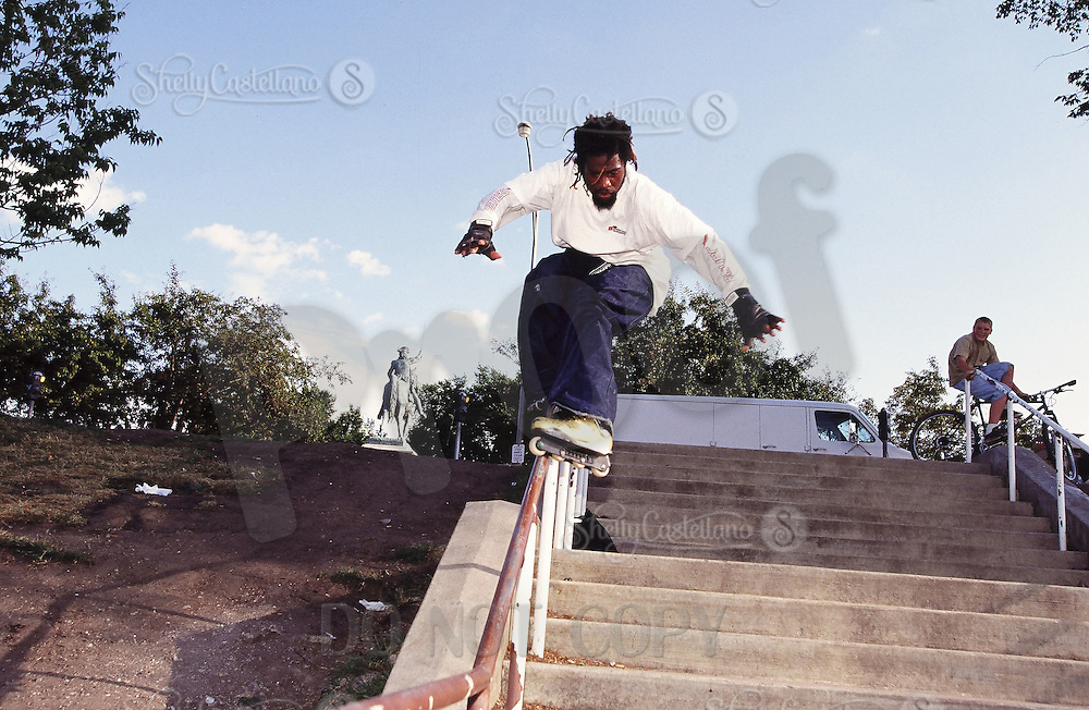 1996:  Pro inline skater AJ Jackson riding the rail down a set of stairs near Lake Michigan in Chicago, IL.  Transparency Image Scan.