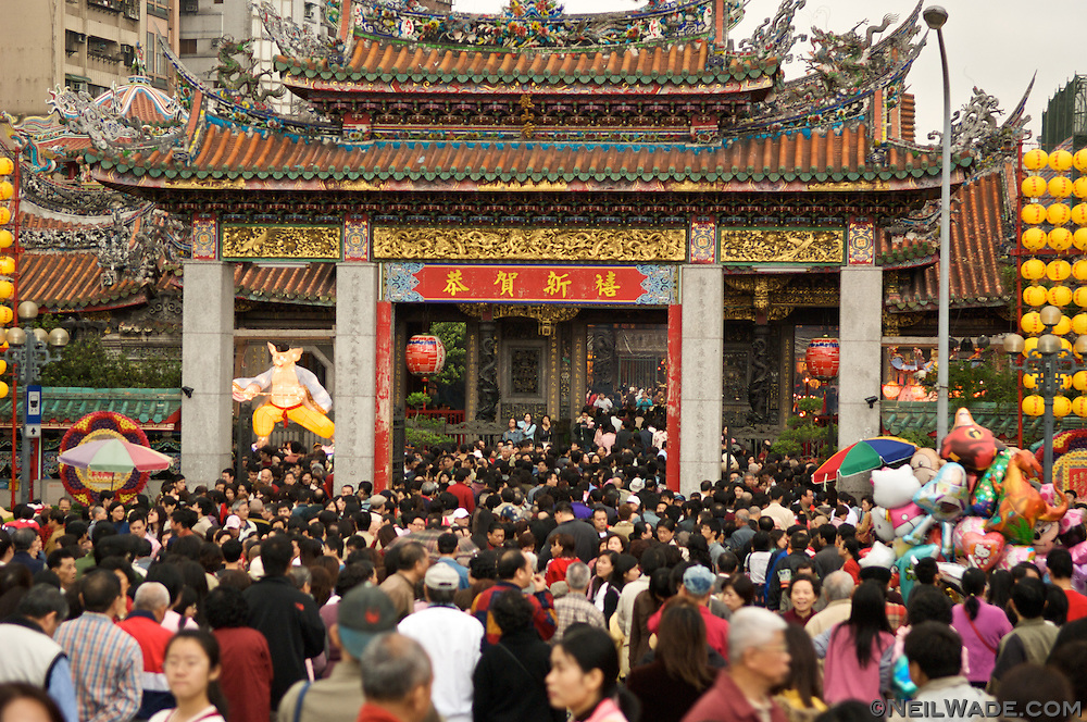 A crowd of people gather in the rain at Longshan Temple for Chinese Lunar New Year 2007.