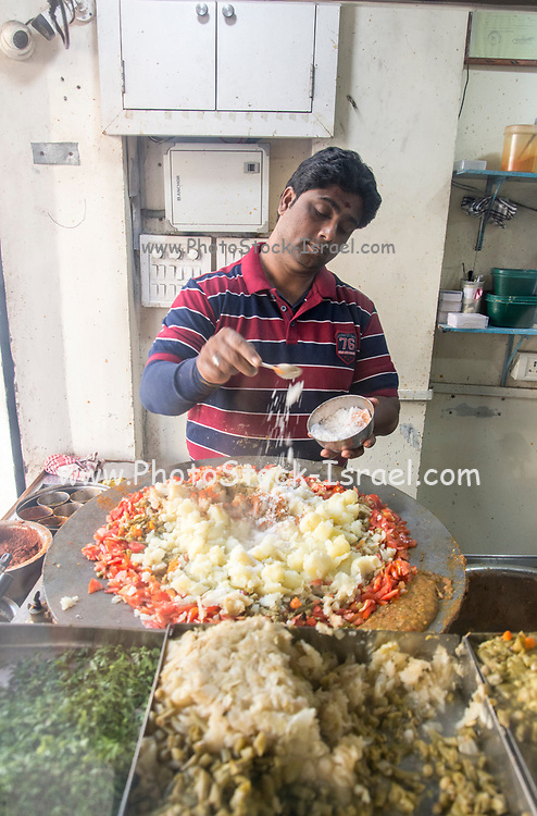Preparing and selling Indian street food in a food stall. Photographed in Ahmedabad, Gujarat, India