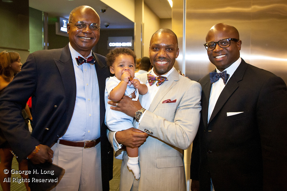 "WDSU-TV's Norman Robinson and General Manager Joel Vilmenay flank Dr. Andre Perry holding his son at the ""Close Ties"" movie premier at The Theatres at Canal Place"""
