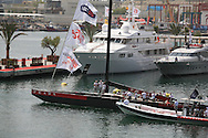 Tender prepares to tow Italy's Team Luna Rossa past megayacht dock in Port America's Cup to join afternoon of America's Cup fleet racing; Valencia, Spain.