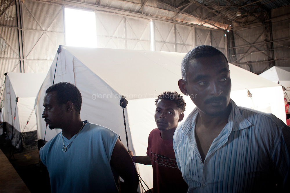 HAL FAR, MALTA - JUNE 21: Dawit (right), a 35 years immigrant old from Ethiopia, and Michael (center), a 25 years old immigrant from Eritrea, are here by the Swiss Red Cross tents inside the Hangar Open Center in Hal Far (which translates as &quot;Rat's Town&quot;) on June 21, 2011. <br /> <br /> Dawit was a language teacher in Tripoli and lived well, with no problems until the crisis started. He arrived in Malta on March 29th on a boat with 80 people after crossing the sea for 34 hours. &quot;Once the UN resolution against Libya was signed there were State TV announcements (also in English) that announced that migrants were free to leave the country. It wasn't possible before that date because of the agreement between Italy and Libya&quot;. No police or army forced them to leave, but there was some kind of general pressure to get sub-saharan migrants out of the country and to have them leave by boat. In Dawit's case, his landlord told him he had one day to leave his apartment. &quot;Buses in Tripoli were collecting people and deporting them&quot;, Dawit says. They couldn&rsquo;t go towards Tunisia or Egypt, only towards to the coast. Other sub-Saharans were able to flee to Tunisia, but there aren't any Ethiopian embassies in Libya, so Ethiopians in Libya don't have any documents that allowed them to stay in the country or officially cross borders. Once they arrived at the port they didn't pay any fixed fee but all they had was confiscated, including food and water. A boat was given to them and they left. &quot;People had bought food and water for their journey, but everything was confisfacted. I was lucky, because it took me only 34 hours to arrive in Malta, but it took these guys (indicating Michael, 25, and Mubarak &ndash; not in this picture -, 23, both from Ethiopia, standing next to him) 10 days to arrive&quot;, Dawit says. Michael, 25, stands next to Dawit. He was on a boat with his wife and two twins and arrived in Malta on April 12. It took him 10 days to arrive. They had no food and no water. They fed their 12 mont