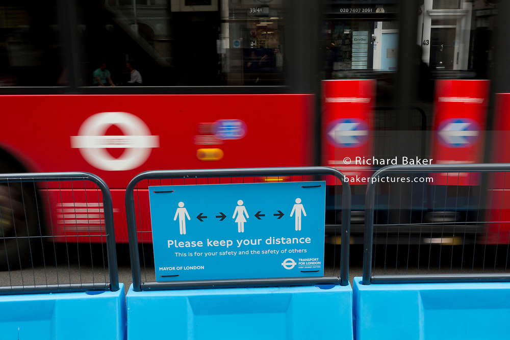 As the UK's Conornavirus pandemic lockdown continues, but with travel restrictions and social distancing rules starting to ease after three months of closures and isolation, a London bus blurs past a social distance road sign where the road has been narrowed in favour of wider pedestrian pavements at Borough, on 9th June 2020, in London, England.