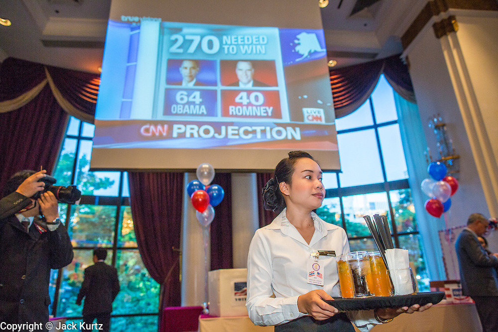 07 NOVEMBER 2012 - BANGKOK, THAILAND: A hotel waitress stands under a giant TV screen showing CNN's election coverage at the US Embassy's election watch party in Bangkok. US President Barack Obama won a second term Tuesday when he defeated Republican Mitt Romney. Preliminary tallies gave the President more than 300 electoral votes, well over the 270 needed to win. The election in the United States was closely watched in Thailand, which historically has very close ties with the United States. The American Embassy in Bangkok sponsored an election watching event which drew thousands to a downtown Bangkok hotel. American Democrats in Bangkok had their own election watch party at a restaurant in Bangkok.       PHOTO BY JACK KURTZ