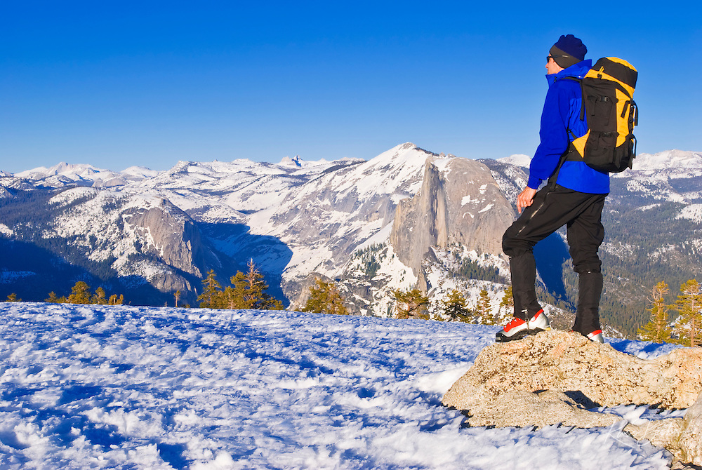 Backcountry skier and Half Dome from the summit of Sentinel Dome, Yosemite National Park, California