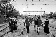 21 April 2016, Greece, Idomeni - A group of refugees walk along the tracks for leave the Idomeni camp with your luggage.