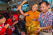 27 JULY 2013 - BANGKOK, THAILAND:  A Buddhist monk blesses the Red Shirt crowd at the birthday celebration for Thaksin Shinawatra. The Red Shirts celebrated former Prime Minister Thaksin Shinawatra's 64th birthday with a party at Phibun Prachasan School in Bangkok. They had a Buddhist Merit Making Ceremony, dinner, cake and entertainment. Most of the Red Shirt political elite traveled to Hong Kong for a party with Thaksin. Thaksin, the former Prime Minister, was deposed by a coup in 2006 and subsequently convicted of corruption related crimes. He went into exile rather than go to jail but remains very popular in rural parts of Thailand. His sister, Yingluck Shinawatra is the current Prime Minister and was elected based on her brother's recommendation.    PHOTO BY JACK KURTZ