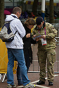 A soldier of the Royal Artillery regiment in the British army helps tourists while standing guard the entrance to  the volleyball venue in central London next to the IOC rings logo on day 4 of the London 2012 Olympic Games. A total of 18,000 defence personel were called upon to make the Games secure following the failure by security contractor G4S to provide enough private guards. The extra personnel have been drafted in amid continuing fears that the private security contractor's handling of the £284m contract remains a risk to the Games.