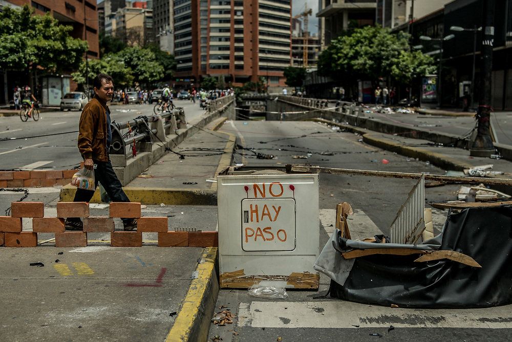 CARACAS, VENEZUELA - JULY 30, 2017:  People walk by barricades constructed by anti-government protesters who oppose today's election for a new National Constituent Assembly. Many fear that today's election for a new National Constituent Assembly will turn Venezuela similar to Cuba. Lines to vote for the new National Constituent Assembly's candidates were significantly shorter across Caracas than those of the opposition's July 16th symbolic vote against the new assembly. Nonetheless, the government reported on state television that millions had turned out to vote. Opponents of the government criticize President Maduro for calling for this election - saying the new assembly is a power grab, and will be a puppet of the President - the only candidates on the ballot are government loyalists. Critics also fear the new assembly will turn the country into a dictatorship, re-write the constitution and wipe out the democratically elected and opposition controlled congress. There have been widespread reports of voter intimidation, and of the government threatening state workers and citizens that receive government benefits like subsidized food - who report the government telling them they are obligated to vote, and if they don't, they will lose their jobs and benefits. Thousands have taken to the streets to protest the election in the days leading up to the July 30th vote.  PHOTO: Meridith Kohut for The New York Times