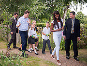 ***EMBARGO 12.01AM Tuesday 17 June.*** © Licensed to London News Pictures. 12/06/2014. Wallington, UK. (Adults L-R) Local MP Tom Brake, Nick Clegg, Lorraine Pascale and Headteacher Havard Spring [sic] walk through the school's vegetable patch with the schoolchildren.  Ahead of an announcement on new food standards for schools, Deputy Prime Minister Nick Clegg and celebrity chef Lorraine Pascale visit Foresters Primary School where they picked fruit with schoolchildren from the school's vegetable patch, prepared a fruit salad, helped the school chefs to serve food and sat with the children as they ate lunch. Photo credit : Stephen Simpson/LNP