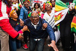 "Lodon, February 21st 2015. Dozens of exiled Zimbabweans gather outside their embassy in London proclaiming Mugabe's last birthday in office. Singing and dancing as they have done every Saturday since 2002, the group spoke with passersby and added yet more names to their petition. PICTURED: ""Mugabe"" re-enacts his recent fall, made famous for the internet memes it generated."