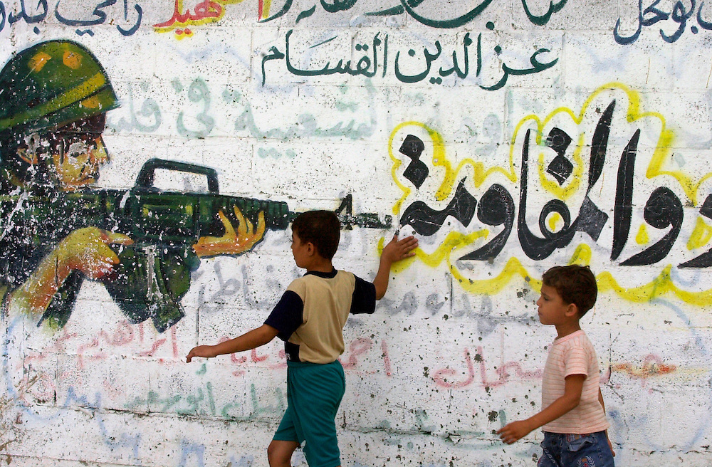 A Palestinians boy runs his hand by a  wall with graffiti depicting a soldier shooting at a Palestinian boy (out of the frame) at the Beach refugee camp Sunday July 29, 2001.  Graffitti has become a popular way to express emotions and catalogue the last 10 months of fighting. The paintings are a visual journey through an uprising that has left nearly 700 people dead, more than 550 of them Palestinians.