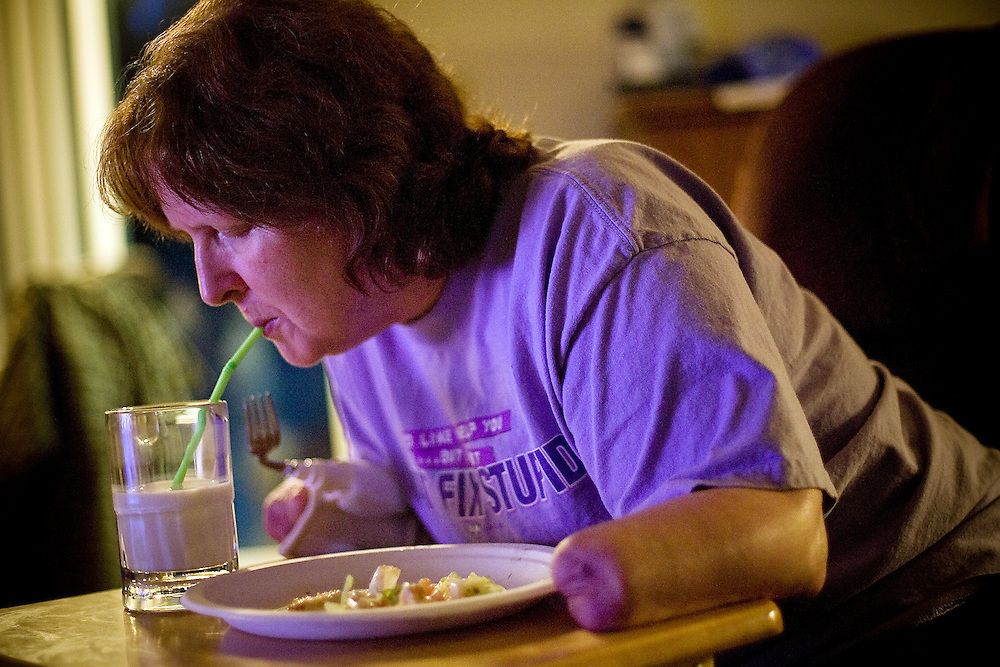 JEROME A. POLLOS/Press..Kim Houx takes a sip of milk while eating dinner with her husband recently at their home in Post Falls. About seven months ago, Kim was rushed to the hospital with a severe staph infection that affected her heart. Within a month, her feet and hands were amputated.