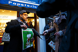 © Licensed to London News Pictures. 16/01/2015. LONDON, UK. A man talking to a TV crew with a copy of Charlie Hebdo's survival edition after buying it from 'The French Bookshop' in London on Friday, 16 January 2015. Photo credit : Tolga Akmen/LNP