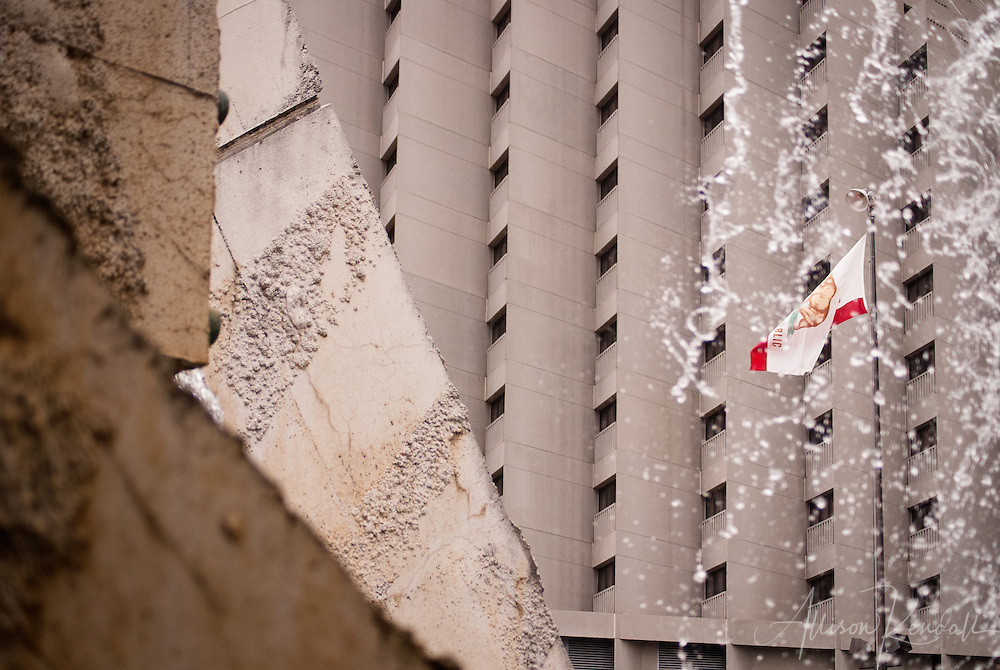 The concrete and steel bones of downtown San Francsico structures contrast with falling water from a fountain in Levi's Plaza, and the gentle wave of the California state flag