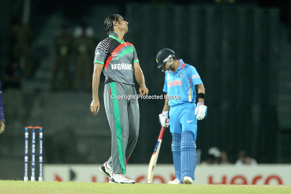 Shapur Zadran reacts after bowling with Virat Kholi in the background during the ICC World Twenty20 match between India and Afghanistan held at the Premadasa Stadium in Colombo, Sri Lanka on the 19th September 2012<br /> <br /> Photo by Ron Gaunt/SPORTZPICS