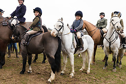© Licensed to London News Pictures. 26/12/2018. London, UK.  Children on their ponies at the traditional Chiddingfold, Leconfield and Cowdray Boxing Day Hunt sets off from the kennels at Petworth House in Petworth Park, West Sussex.  Photo credit: Vickie Flores/LNP
