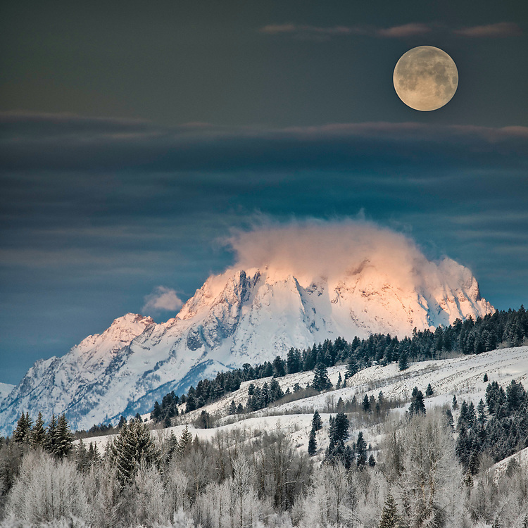 A winter full moon setting behind Mount Moran in the Teton Range.